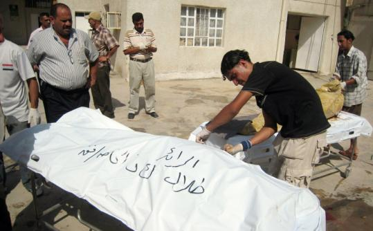 Iraqi hospital workers identified and covered bodies of victims of a suicide bombing yesterday in Baqubah. The bomber, a woman, blew herself up outside the city's courthouse.