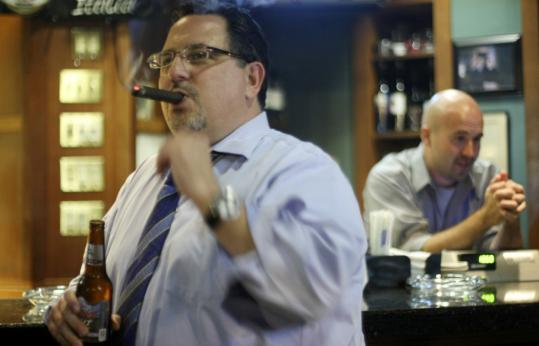 Raymond Mansolillo, who puffed on a stogie at Churchill's Lounge in Boston Tuesday night, said city smoking regulations are ''killing small businesses.'' Behind him, Joe Murphy tended the bar.