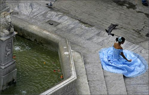 See more photography at Boston.com/photos A young woman celebrating her 15th birthday poses for a photographer on the steps of a fountain in Old Havana, Sunday, Sept. 28, 2008.