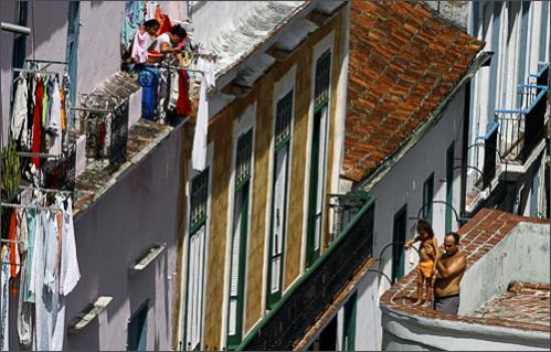 See more photography at Boston.com/photos A man holds a girl on his rooftop as they look over the edge in Old Havana, Sunday, Sept. 28, 2008.