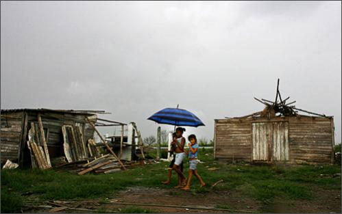 See more photography at Boston.com/photos Girls walk by homes damaged by hurricanes Ike and Gustav in Los Palacios, Cuba, Saturday, Sept. 20, 2008. Ike and Gustav caused US $5 billion damage to Cuba this month.