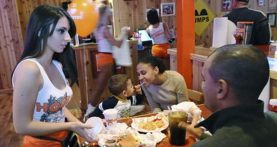 Waitress Stephanie Castater, wearing the familiar Hooters uniform, takes an order from one of the many families at the new restaurant in Saugus.