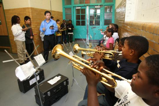 Jerry Chu directs the 5-year-old Thomas J. Kenny Elementary School marching band and fifth-grader Jean Catulle (lower right).