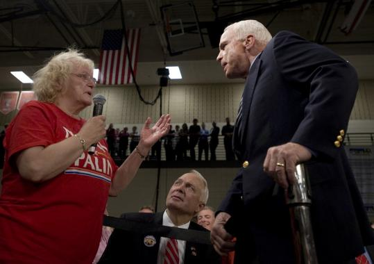 Senator John McCain took a question from a supporter who called Senator Barack Obama an Arab during a town hall meeting in Lakeville, Minn., yesterday. He took the microphone from her and called his rival ''a decent family man.''