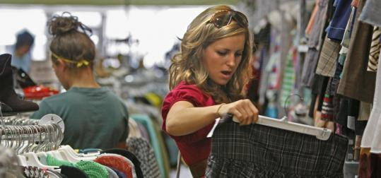 Student Kristina Marquez looks at a skirt from a rack of new and used clothes at Buffalo Exchange in Fullerton, Calif. Many such shops nationwide are seeing a rise in business.