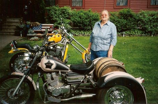 Margaret ''Peggie'' Blais stood behind her beloved three-wheeled, pink and black motorcycle last summer. An accident on the bike last week in Danvers injured her right arm in multiple places, broke her left leg, and caused severe facial lacerations.