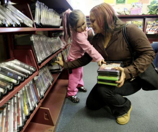 At Everett's Parlin Memorial Library, Melissa Farfan picks movies with daughter Sarah, 4.