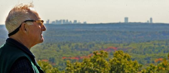 Al French gazes out over a tree canopy towards Boston's skyline from Holt Hill on the Ward Reservation in Andover.