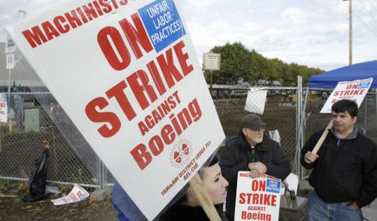 Striking Boeing machinists walk the picket line at a plant in Renton, Wash. Their main issue in contract negotiations, which broke off Monday, is job security.
