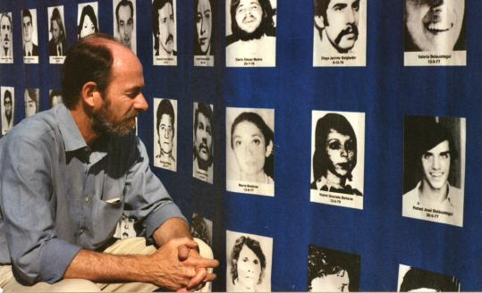 ''Our Disappeared'' filmmaker Juan Mandelbaum looks at images of the Belaustegui children on a tarp with pictures of other missing persons at Memory Park in Buenos Aires.