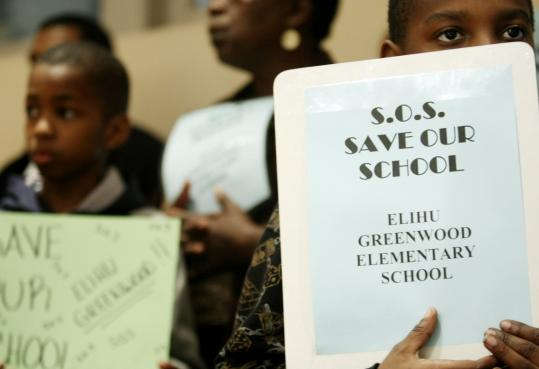 Wilson Petitfrere (right), an 8-year-old third grader at the Elihu Greenwood Elementary School, held up a sign at last night