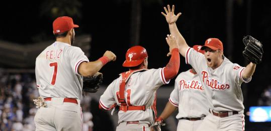Phillies closer Brad Lidge (right) celebrates with Carlos Ruiz and Pedro Feliz after the final out.