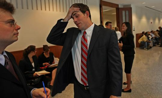 Harvard University law student Nick Hartigan (right) talks with another student attorney, Mitch Stromberg, at Housing Court in Boston.