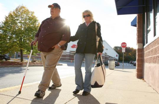 Jim Agostinelli and Barbara Drew, who are blind, in Stoneham yesterday. They are losing their jobs because of state cuts.