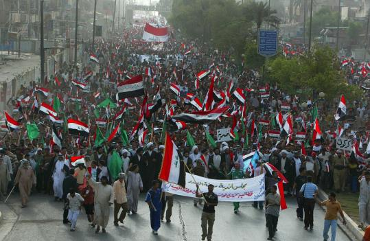 Shi'ite demonstrators carried Iraqi flags during a protest yesterday against a proposed US-Iraq security pact in Baghdad. As many as 20,000 shouted anti-American slogans in the streets.