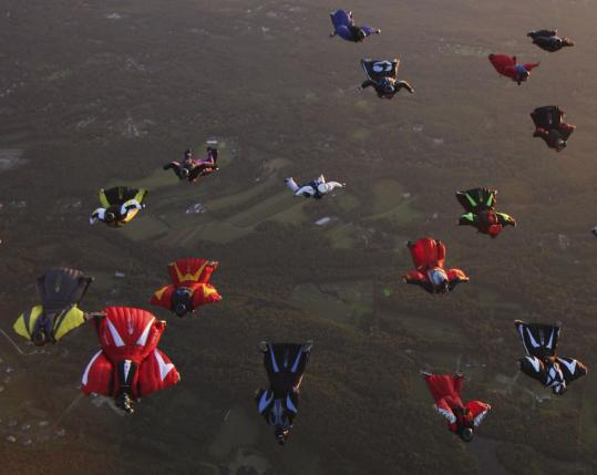 A flock of wingsuiters (above) led by Jeff Nebelkopf journey back to earth after leaping out of a plane in Pepperell (below, right).