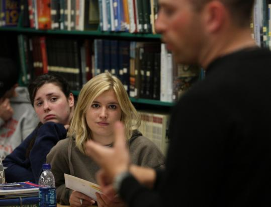 Kim Hayward (left) and Samantha Colarusso listened to Danny Barr, an assistant admissions director at UMass-Amherst, last week at Arlington High School. Barr stressed the lower tuition.