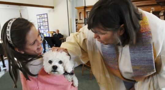 Katharine Garnett, 9, of Madison, Conn., held her dog, Chester, as minister Nancy Haverington offered a blessing during the blessing of the animals ceremony at the First Parish