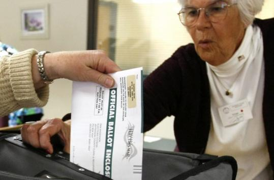 EARLY BIRD GETS THE VOTE - A Jefferson County election judge watched a voter drop her marked ballot into the ballot box during early voting in Westminster, Colo. Early voting continues in Colorado