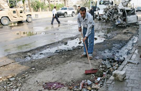 A man swept debris from the gutter as a damaged car was towed away after a suicide car bomb targeting a government convoy in the Bab al-Sharji area of central Baghdad yesterday. The Iraqi military said nine people were killed and 26 wounded.