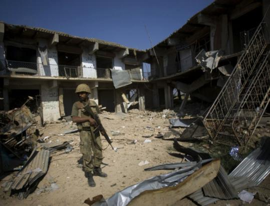 Pakistani soldier guarded damaged houses in the village of Loi Sam after a long and bloody struggle with militants.