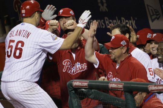 Joe Blanton is congratulated by his mates not for his pitching, but for a home run in the fifth.
