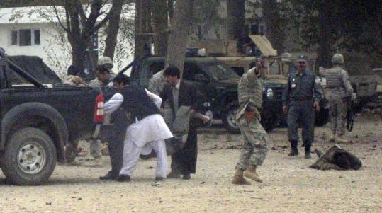 Security personnel carried a wounded man in Baghlan Province yesterday minutes after suicide attack. One US soldier was killed in the attack; two others were wounded.