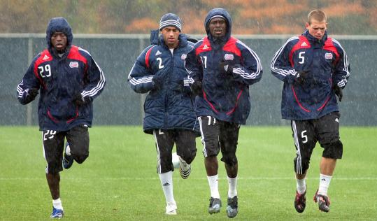 Rain didn't keep (from left) Kenny Mansally, Amaechi Igwe, Kheli Dube, and Joe Germanese from taking to the practice field.