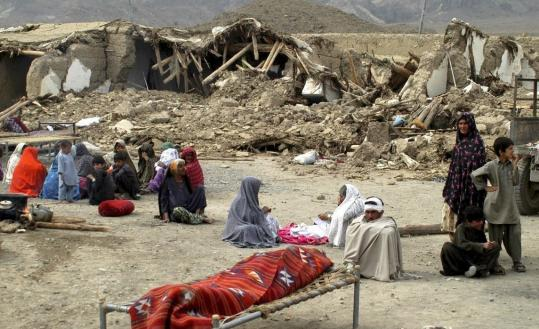 A Pakistani villager (sitting at center right) looked at the body of a family member killed by yesterday's magnitude 6.4 earthquake as others sat in front of their ravaged homes in Ziarat.