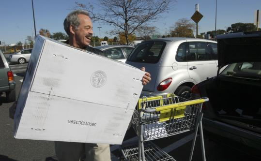 Mac Mendelsohn packs up his car at a Boston shopping center. Like other drivers he's enjoying paying less at the gas pump these days.