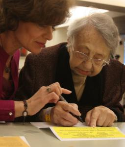 Alexandra Dashevskaya assists Tsiliya Braz, 107, with her absentee ballot at the Hebrew Rehabilitation Center.