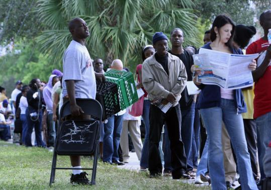 A volunteer handed out chairs and milk crates as early voters waited in long lines in Miami yesterday.