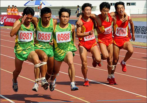 Two months after China's elite athletes dazzled the world at the Beijing Olympics, its 750 million peasant farmers are taking their turn in the sporting spotlight this week at the 6th National Peasant Games in Quanzhou. Events include the unwieldy sounding 'Quickly Harvest the Grain and Get it Into Storage,' tire-pushing, a tug-of-war, and pond fishing, to go along with more traditional sports like basketball. Here Chinese farmers race in the '100 metre three person four leg' event on October 28, 2008. See more photography at Boston.com/photos