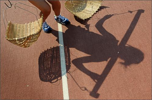 A female Chinese farmer prepares to start a race to plant rice at the 6th National Peasants Games in the city of Quanzhou on October 28, 2008.