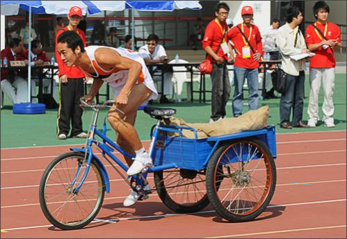 A Chinese farmer rides a tricycle during a grain gathering race at the 6th National Peasants Games in the city of Quanzhou on October 28, 2008.