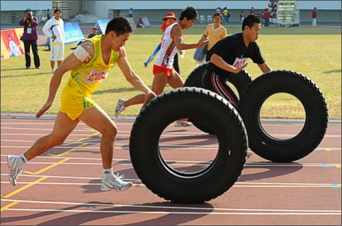 Chinese farmers sprint during the 100 metre tire-pushing event at the 6th National Peasants Games in the city of Quanzhou on October 28, 2008.
