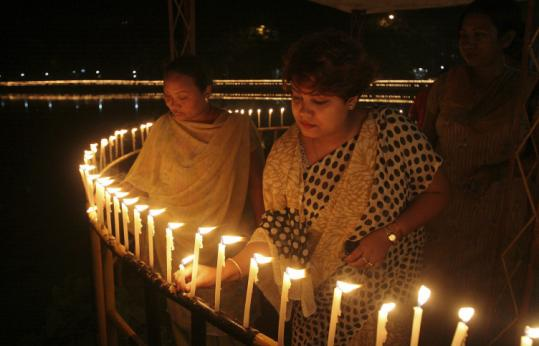 Women in Gauhati, India, lighted candles yesterday to honor 77 people killed in attacks in four towns Thursday.