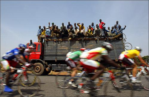 Men on the top of a truck cheer the riders during the 7th stage of the 22nd Tour du Faso cycling race between Yako and Ziniare, Burkina Faso, Thursday, Oct. 30, 2008.