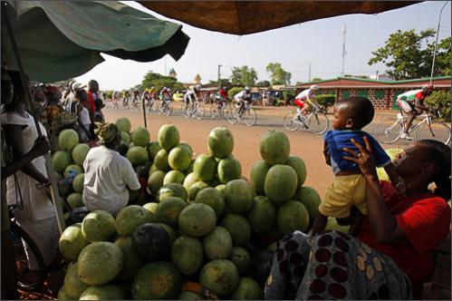 Riders cycle next to a market during the third stage of the 22nd Tour du Faso cycling race in Bobo Dioulasso, Burkina Faso, Sunday, Oct. 26, 2008.