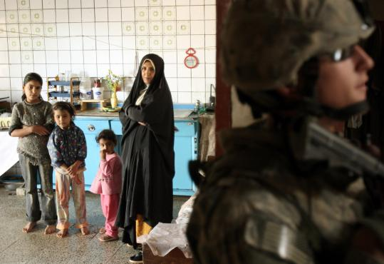Iraqis watched yesterday as US soldiers searched their house for weapons in Baquba, about 40 miles northeast of Baghdad.