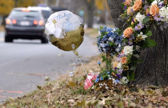 A cross with flowers and a balloon that says ''Thinking of You'' were placed against a tree near where Roberta A. Salois and her son Steven X. Smith-Salois, 9, were killed in Westfield.