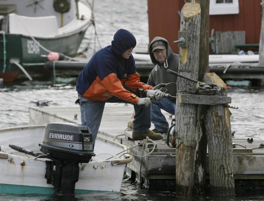 Owen Johnson (left) and his father, Peter, repaired damage yesterday done by waves in Boothbay Harbor.