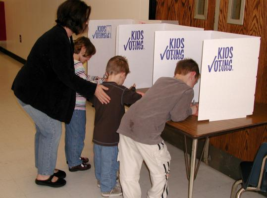 A mother helps her children vote through the Kids Voting Plymouth program on Election Day.