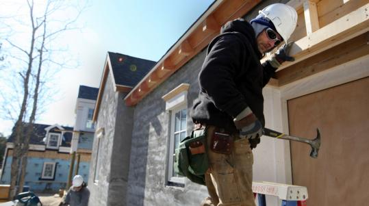 Walter Ford works on the framing of a house at Pinehills development in Plymouth.