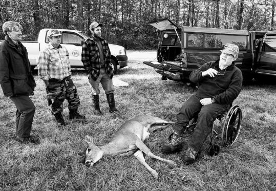 At the Devens hunt, George Wade (right) relates the story of shooting this doe to (from left) Marion Larson of MassWildlife, friend Wendell Smith, and biologist John Sheedy.