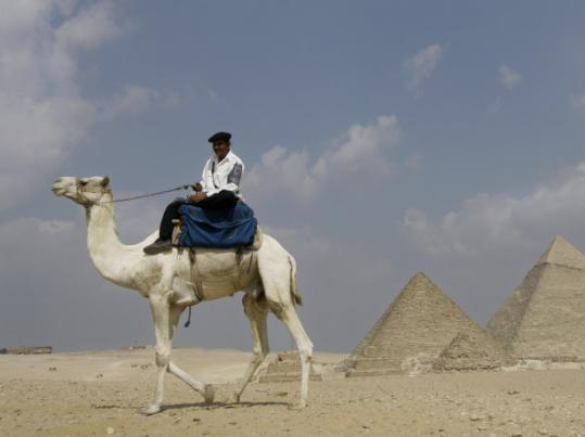 An Egyptian policeman patrols on camel close to the Giza pyramids in Cairo.