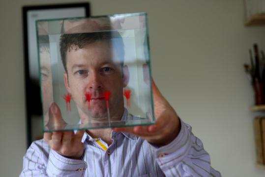 Harvard neuroscientist Bevil Conway, holding a glass box he designed, is looking for the neural basis of our reaction to color.