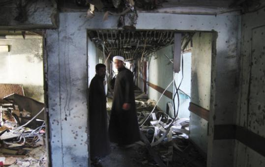 In a suburb of Fallujah, Iraqis inspected the wreckage at a hospital where a suicide bomber killed three people yesterday.