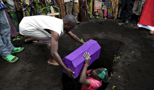 The coffin of a child who died of cholera was lowered into a grave in Kibati, in eastern Congo, yesterday. Fighting in the war-ravaged nation has forced thousands into refugee camps, where poor sanitation has increased the risk of disease.