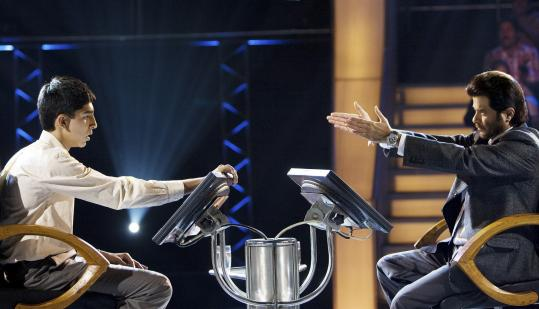 Dev Patel (above, left) plays a kid from an Indian shantytown who becomes a contestant on a quiz show with Anil Kapoor the host in ''Slumdog Millionaire,'' directed by Danny Boyle (below), who spent eight months in Mumbai working on the film.